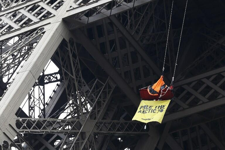 Um militante do Greenpeace pendurado em uma tenta presa ao segundo andar da Torre Eiffel, na capital francesa.