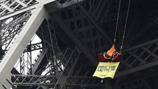 A Greenpeace activist hangs from a tent at the Eiffel Tower