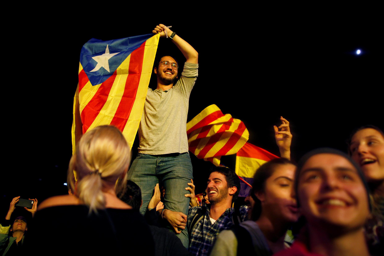 """Un hombre muestra una """"estelada"""", la bandera separatista catalana, en la Plaza Cataluña, Barcelona, luego del referéndum por la independencia el 1 de octubre de 2017."""