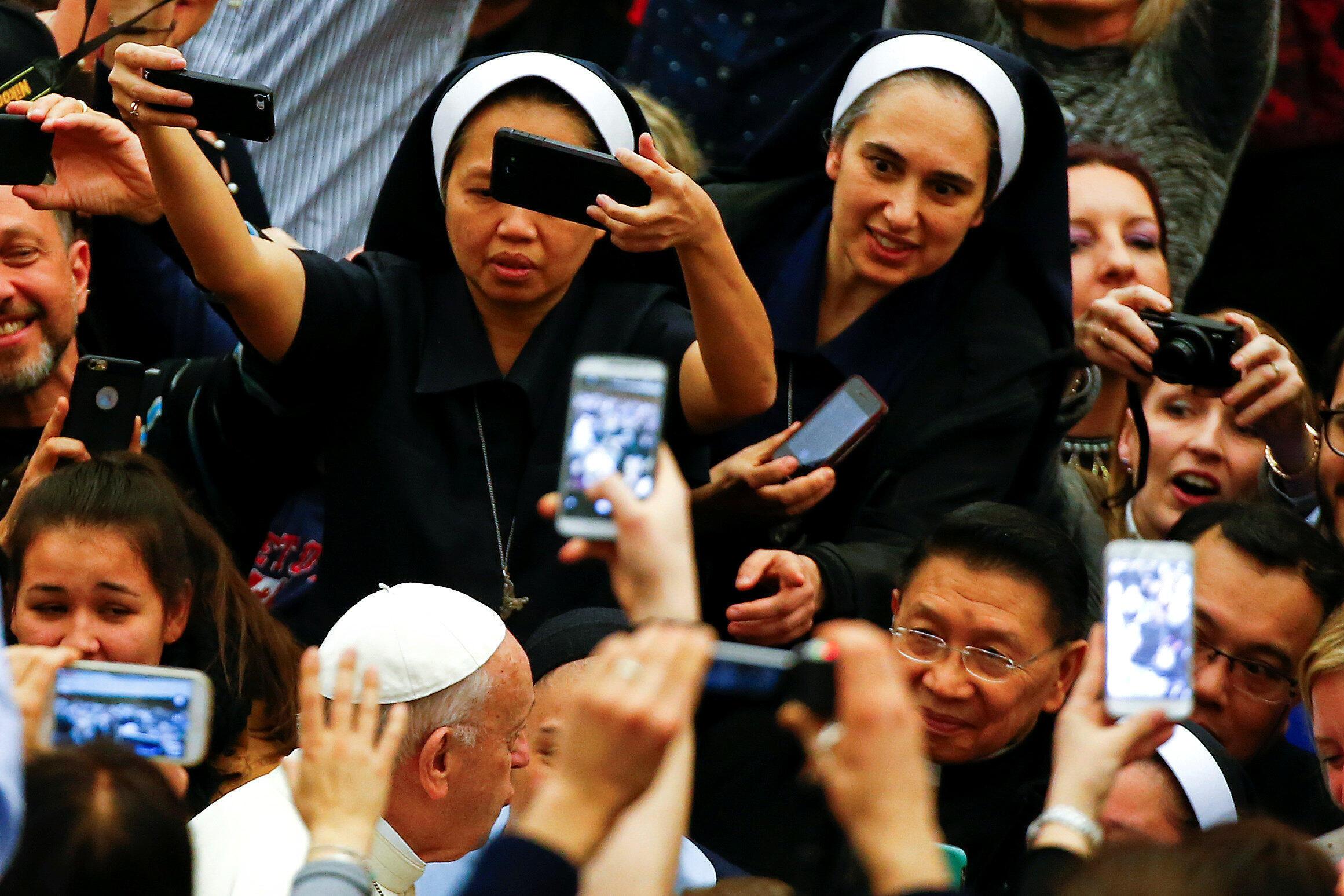 Masu mabiya darikar Katolika na daukan hotunan Fafaroma Francis da ya jagoranci addu'oin bikin Easter a Vatican