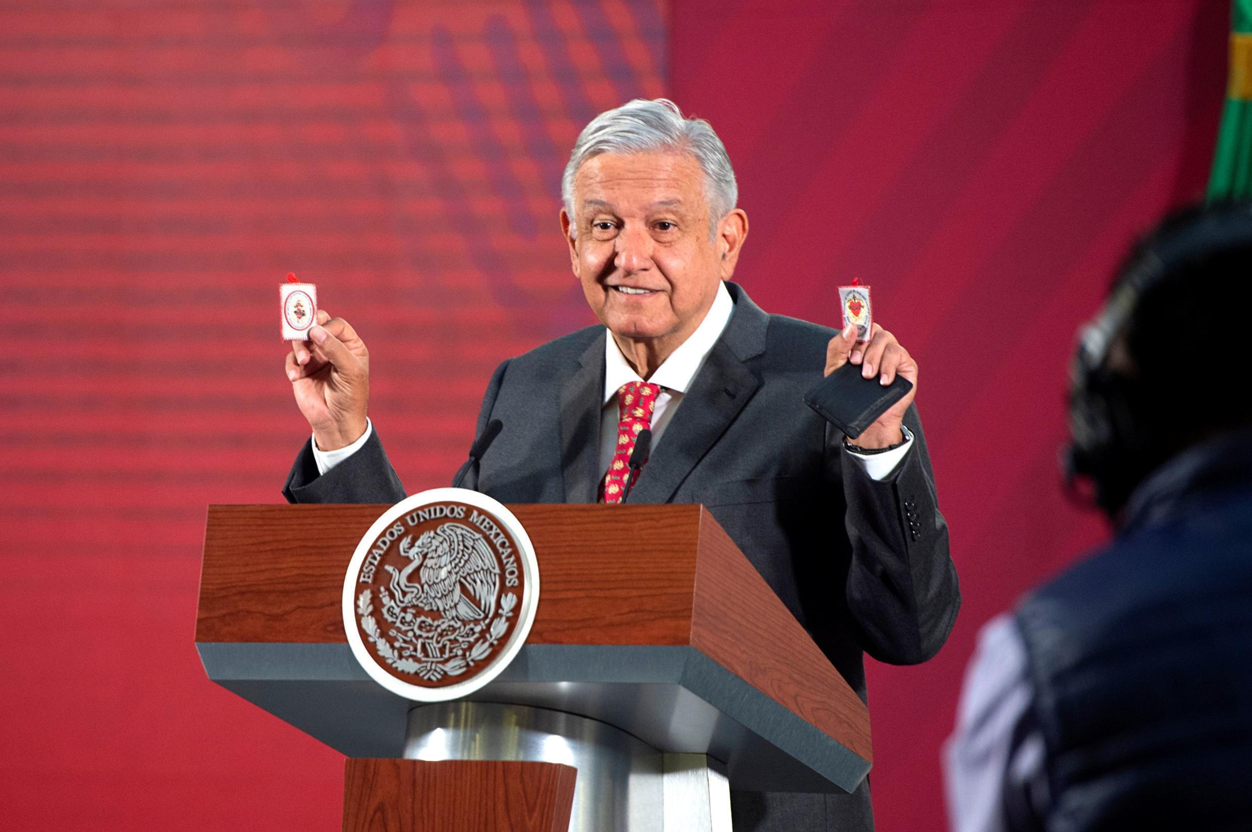 Mexico's President Andres Manuel Lopez Obrador shows his amulets, which he says serves him as a ?protective shield? against the coronavirus disease (COVID-19) along with his honesty and not allowing corruption, during a news conference at the National Palace in Mexico City, Mexico March 18, 2020.