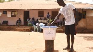 Un jeune homme dépose son bulletin dans l'urne le 10 mars 2019 à Bissau.