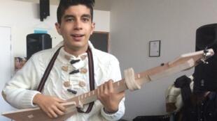 Jordan, 18, plays his simplified guitar at the experimental music workshop