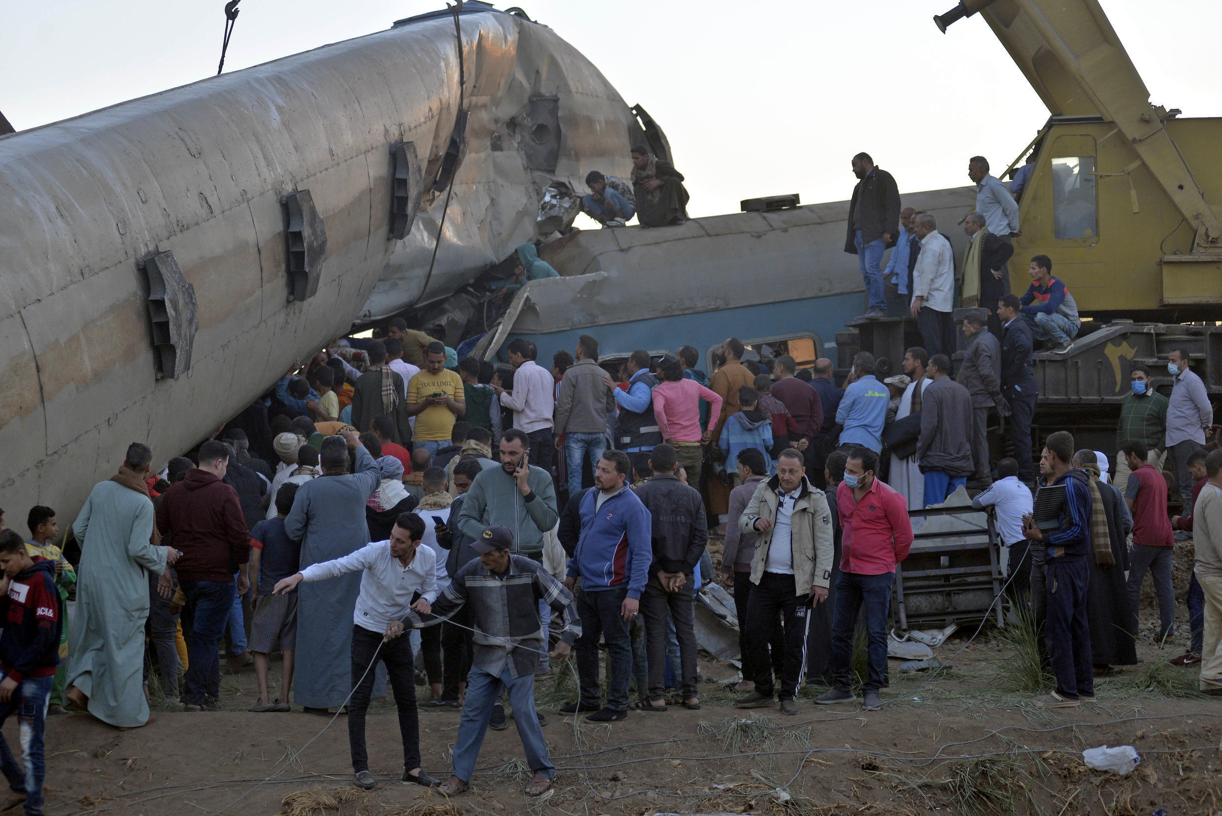 People gather around the wreckage of two trains that collided some 460 kilometres (285 miles) south of the Egyptian capital Cairo, on March 26