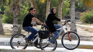 Des vacanciers sur leur bicyclette, sur l'ile de Kish en Iran.