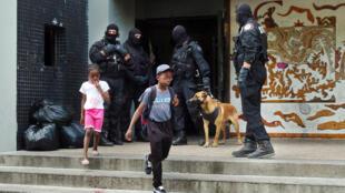 Policiais vigiam a entrada de prédio em subúrbio ao norte de Paris.
