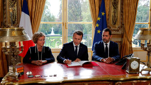 French President Emmanuel Macron signs the decrees accompanied by Labour Minister Muriel Pénicaud (L) and government spokesman Christophe Castaner