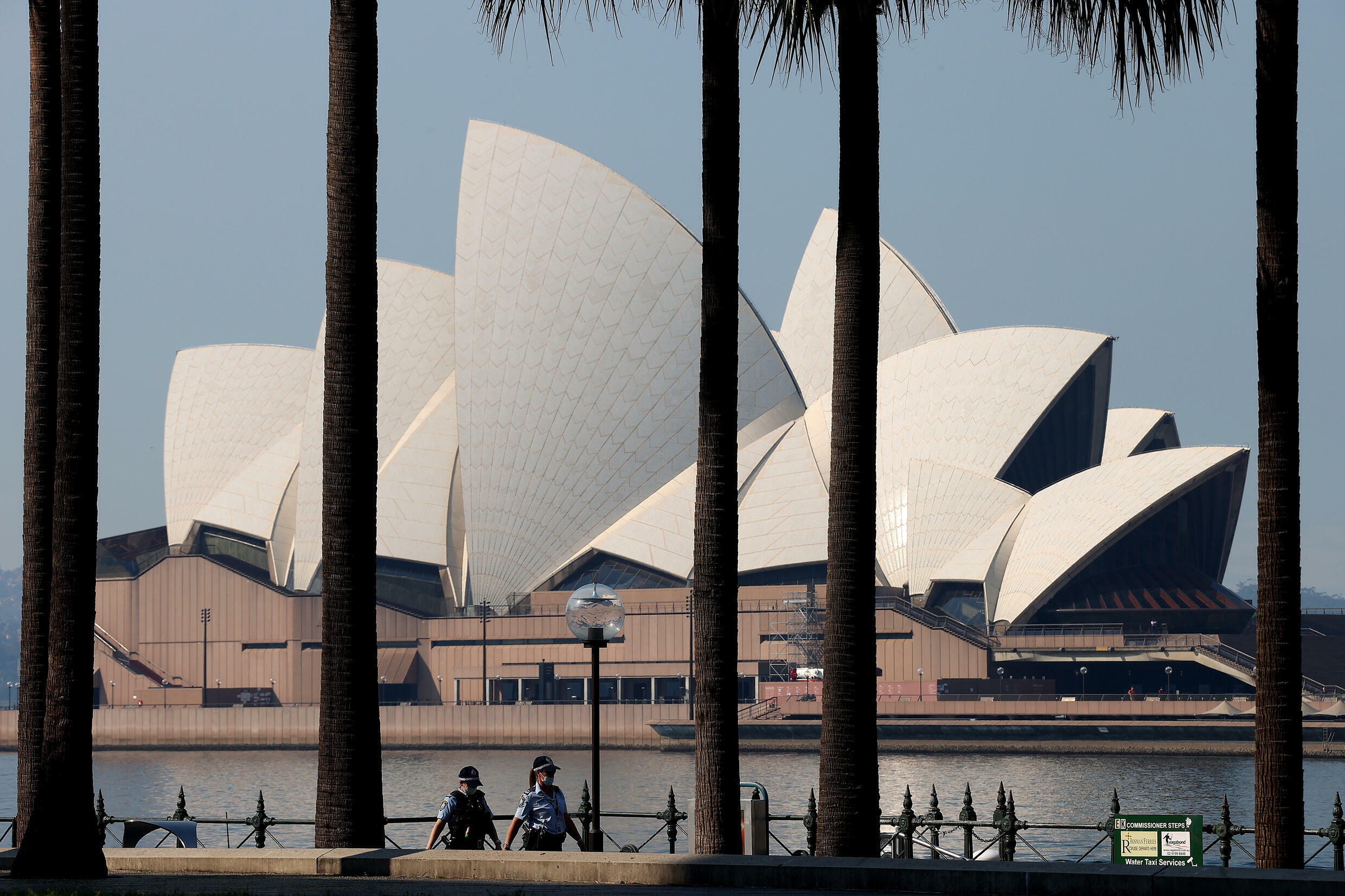 Police officers patrol in front of the Sydney Opera House as the city extends its two-month-old Covid lockdown