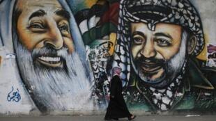 A Gaza, une étudiante palestinienne marche devant une peinture murale représentant Yasser Arafat (d.) et l'ancien leader et fondateur du Hamas, Ahmed Yassin