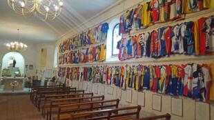 A l'intérieur de la chapelle Notre-Dame-des-Cyclistes, il y a le baptistère, l'autel, la vierge Marie.... et plus de 700 maillots cyclistes multicolores accrochés aux murs.