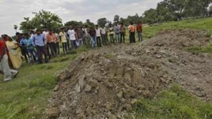 Dân làng tụ tập gần những ngôi mộ các học sinh bị chết do ngộ độc thực phẩm, bang Bihar, Ấn Độ, ngày 18/07/2013