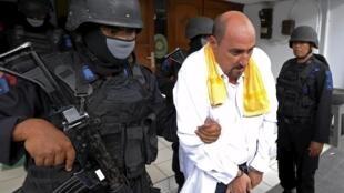 O francês Serge Atlaoui é escoltado por policiais na saída de uma audiência, em 1° de abril