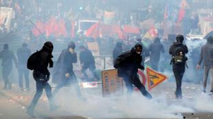 Le gaz lacrymogène flotte autour des manifestants masqués, les BlacK Blocs lors d'affrontements avec la police anti-émeute CRS française, pendant le défilé du 1er Mai à Paris, en France, le 1er mai 2018.