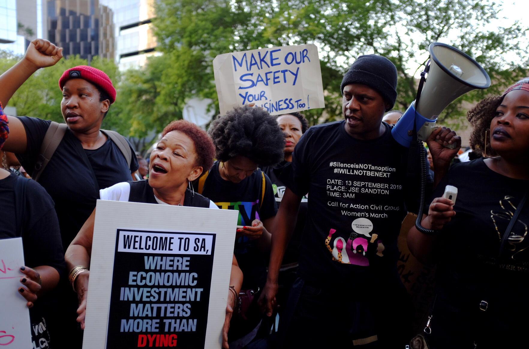 """Femme brandissant une pancarte lors d'une manifestation à la bourse de Johannesburg : """"Bienvenue en Afrique du sud, où les investissements économiques comptent plus qu'une mort."""""""