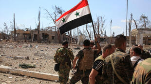 Forces loyal to Syria's President Bashar al-Assad walk at a military complex as one of them holds up a Syrian national flag, after they recaptured areas in southwestern Aleppo on Sunday that rebels had seized last month, Syria.