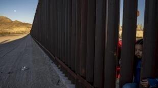 Một cô bé cố len qua 'bức tường' ở biên giới Mỹ-Mêhicô ở Anapra, New Mexico. Ảnh ngày 19/03/2019.