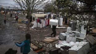 Un homme transporte une machine à laver alors que les gens quittent un camp de Roms à Ivry-sur-Seine, au sud de Paris, le 18 décembre 2014.