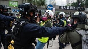 Des policiers repoussent un groupe de journalistes après la dispersion d'un rassemblement à Chater Garden, dans le centre de Hong Kong, le 19 janvier 2020.