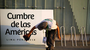 A woman cleans a banner ahead of the eighth Summit of the Americas in Lima, Peru