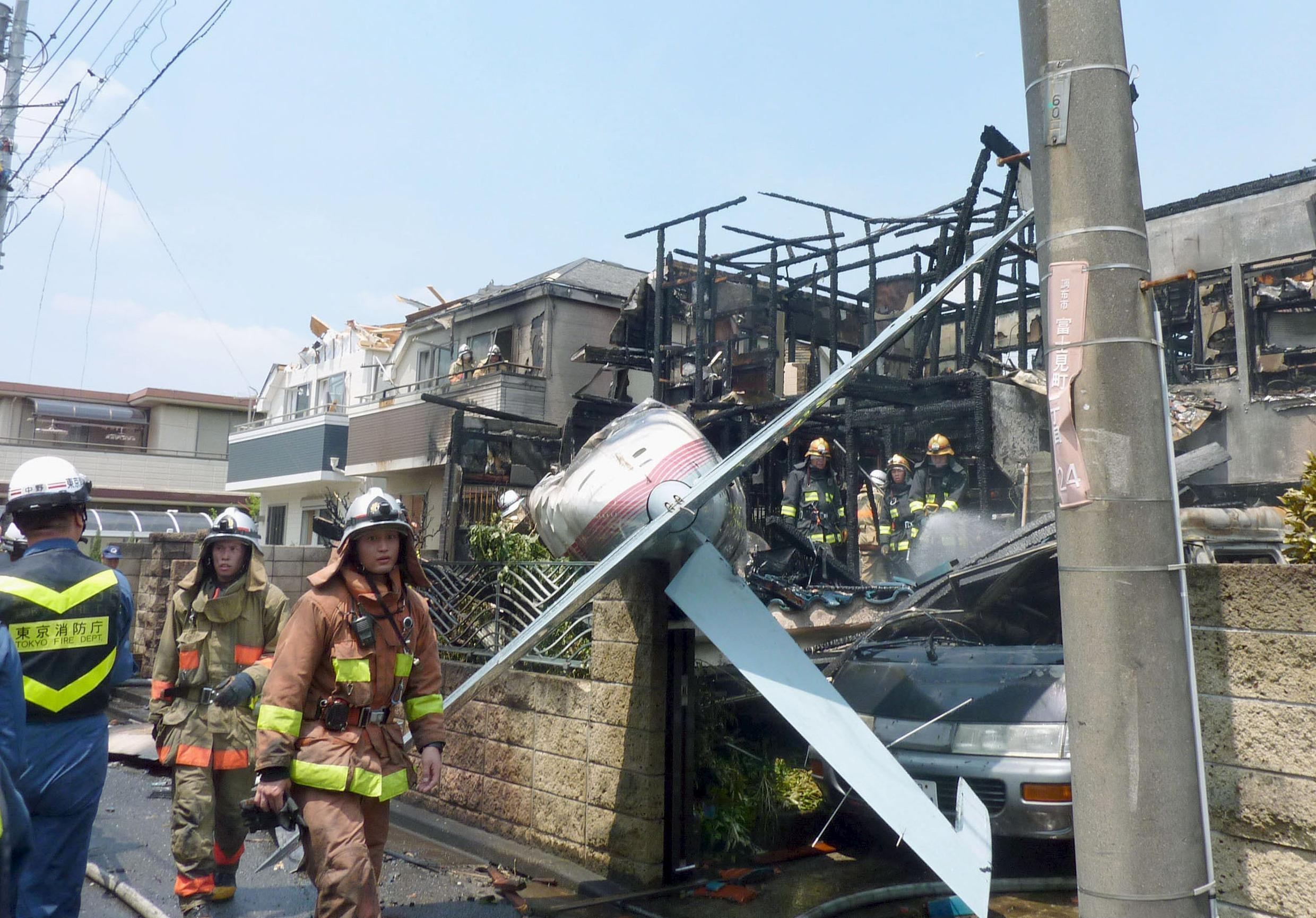 The tail section of a crashed light plane and burning house are seen after the plane went down in a residential area in Tokyo July 26 2015