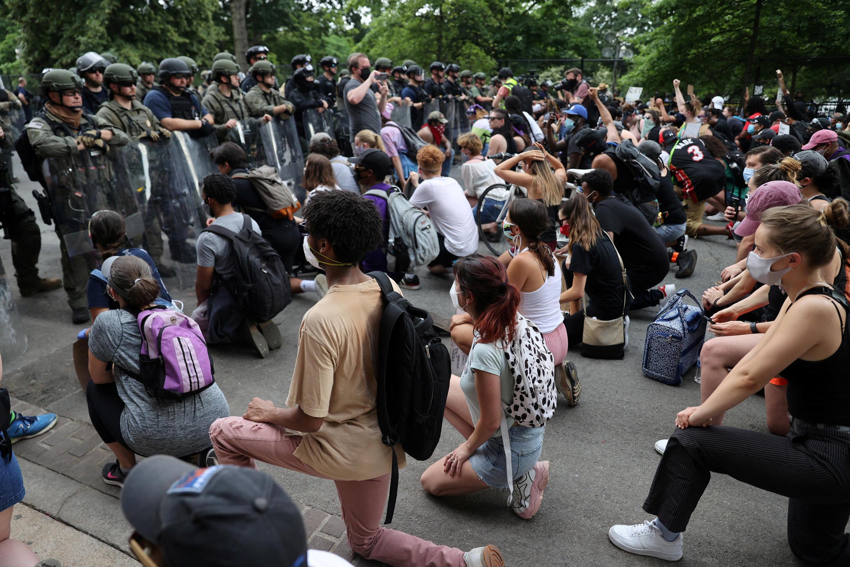Manifestantes ficam de joelhos diante da polícia em protesto contra racismo policial em Washington, no dia 4 de junho de 2020.