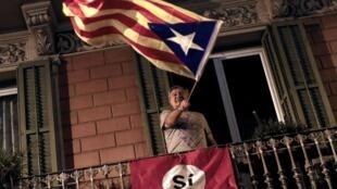 一年前支持西班牙加泰羅尼亞獨立的公民在自家陽台上揮舞分離主義運動的紅、黃、藍三色旗幟    2017年10月1日