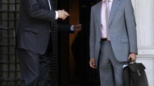 O primeiro ministro Antonis Samaras (e) conversa com o ministro das finanças, Yannis Stournaras