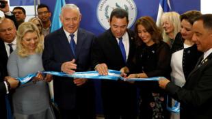 Hilda Patrica Marroquí, esposa del presidente de Guatemala, Jimmy Morales, corta la cinta durante la ceremos en la embajada de Guatemala, junto a su esposo y el primer ministro israelí Benjamin Netanyahu, el 16 del mayo de 2018.