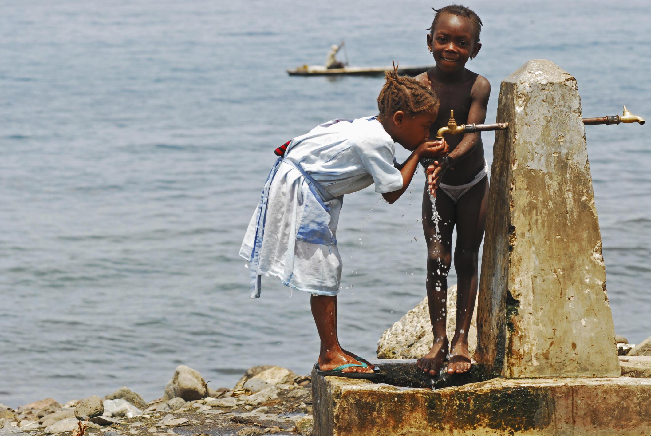 Deux petites filles buvant l'eau du robinet, à Neves, Sao Tomé-et-Principe.