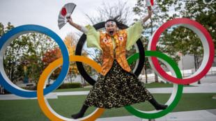 1374289-un-fan-japonais-devant-les-anneaux-olympiques-a-tokyo
