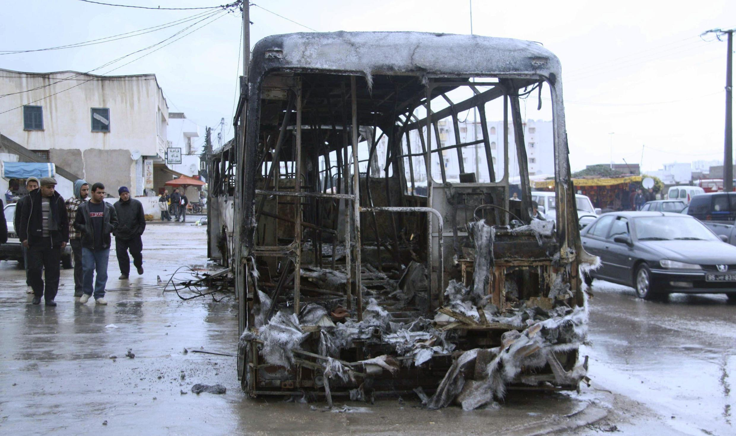 People walk past wreckage of bus which was damaged during recent clashes with police, on main square in Cite Ettadhamen near Tunis