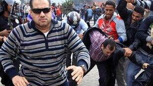 A plainclothes policeman runs to attack a foreign journalist as others beat a protester during a demonstration in Cairo
