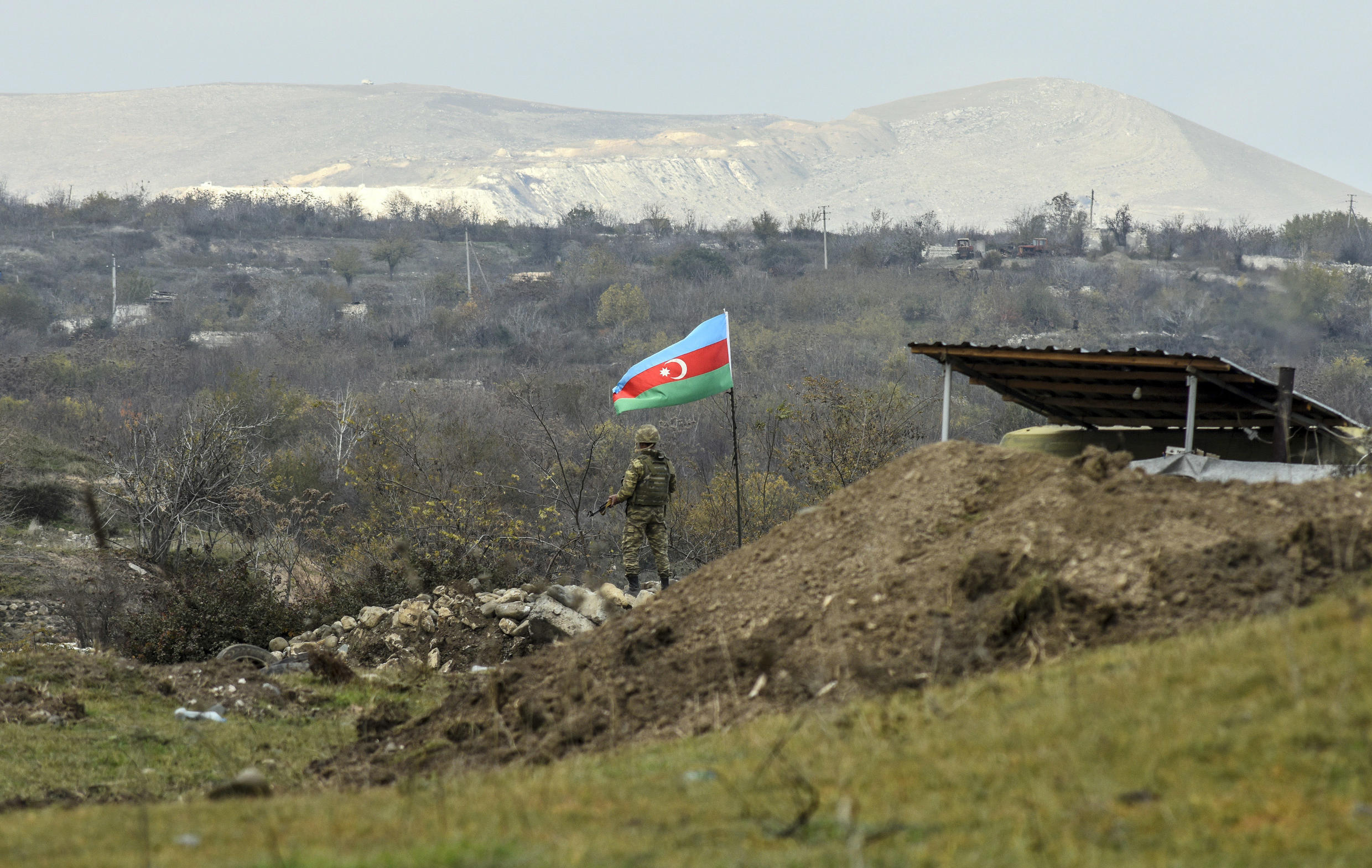 An Azerbaijani soldier stands guard at a checkpoint on a road entering Fizuli from Hadrut on December 2, 2020, a day after Baku's army entered the final district given up by Armenia under a peace deal that ended weeks of fighting over the disputed Nagorno-Karabakh region