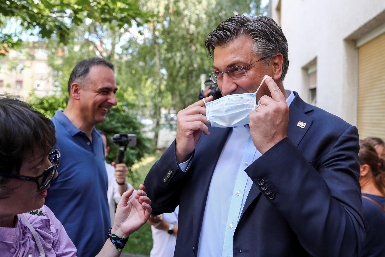 Primeiro-ministro croata, Andrej Plenkovic, coloca uma máscara em frente a uma seção eleitoral de Zagreb, capital da Croácia. (05/07/2020)