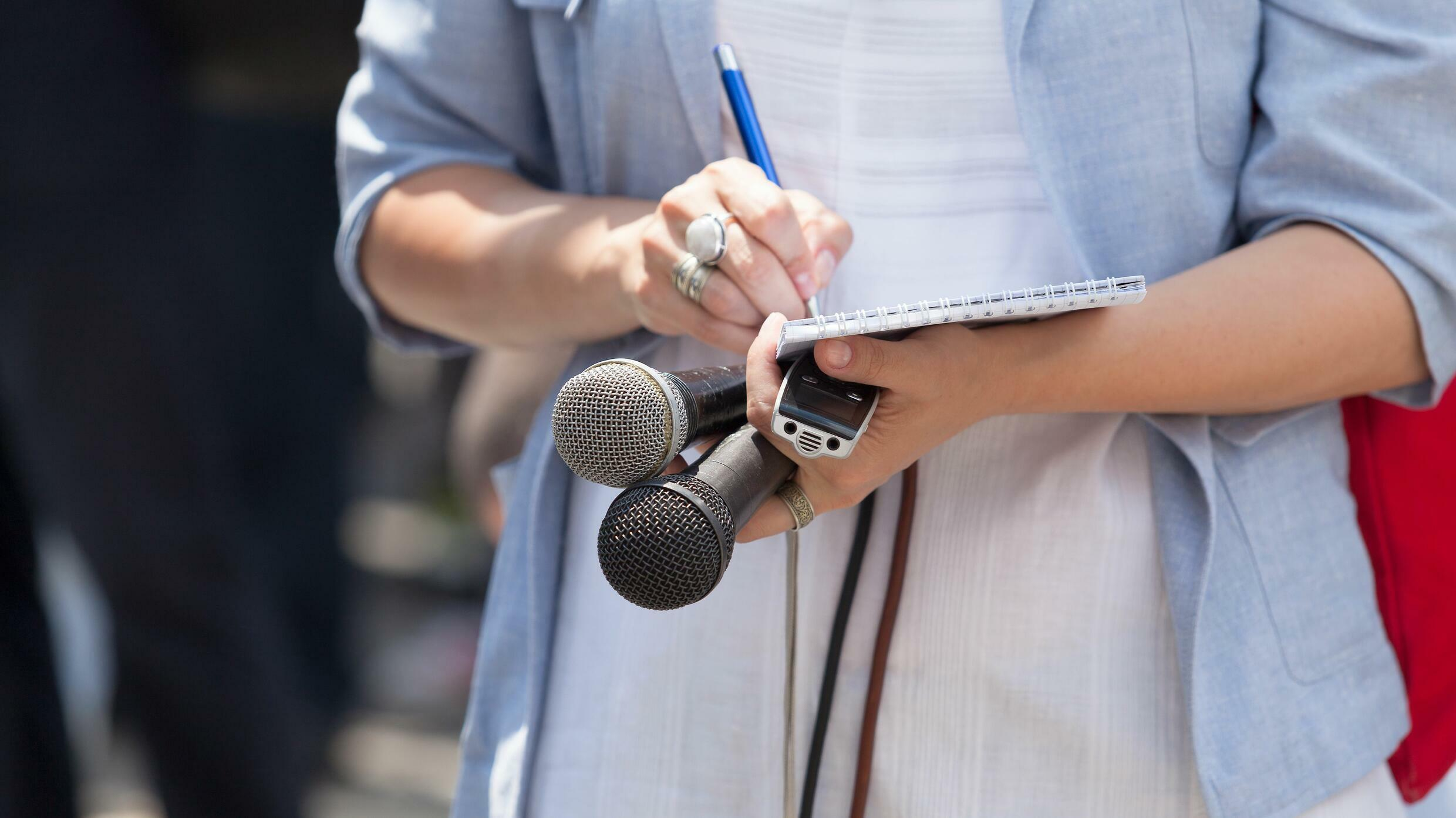 midsection-of-journalist-holding-microphones-while-writing-on-note-pad-878027776-5ae3885e04d1cf003cf1fce5