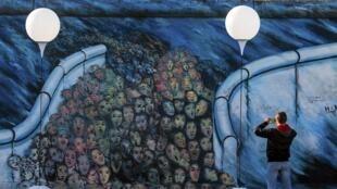 Un homme prend en photo une fresque symbolisant l'ouverture du Mur de Berlin et le passage d'habitants de Berlin-Est vers Berlin-Ouest, peinte sur les restes du Mur.