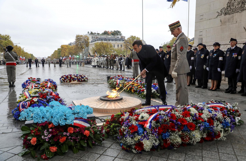 """امانوئل ماکرون، رئیس جمهوری فرانسه، در حال روشن کردن مشعل """"آرامگاه سرباز گمنام"""" امروز یازده نوامبر در پاریس"""