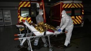 Un pompier des Marins-Pompiers de Marseille portant un équipement de protection transporte une femme de 84 ans soupçonnée d'être infectée par COVID-19, dans une unité COVID-19 à l'hôpital Timone de Marseille.