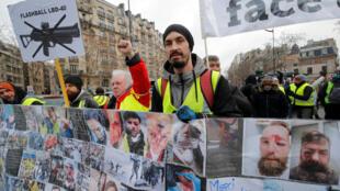 Des «gilets jaunes» se tiennent derrière une banderole où figurent les photos de victimes des violences policières contre leur mouvement, à Paris, le 2 février 2019.