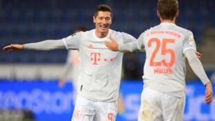 Robert Lewandowski celebrates scoring his side's third goal with Thomas Mueller