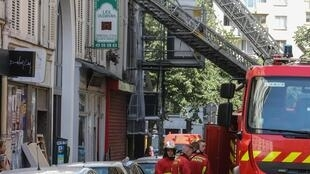 Firefighters in front of a building on rue de Nemours in Paris, where three people died and another was seriously injured in a fire.