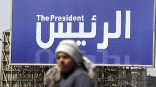 Un hombre camina en El Cairo junto a un cartel que anuncia las elecciones presidenciales.