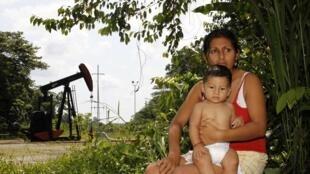 Une femme et son enfant devant leur maison, située juste à côté d'un puits de pétrole appartenant à Chevron, à Lago Agrio en Equateur, le 25 janvier 2011.