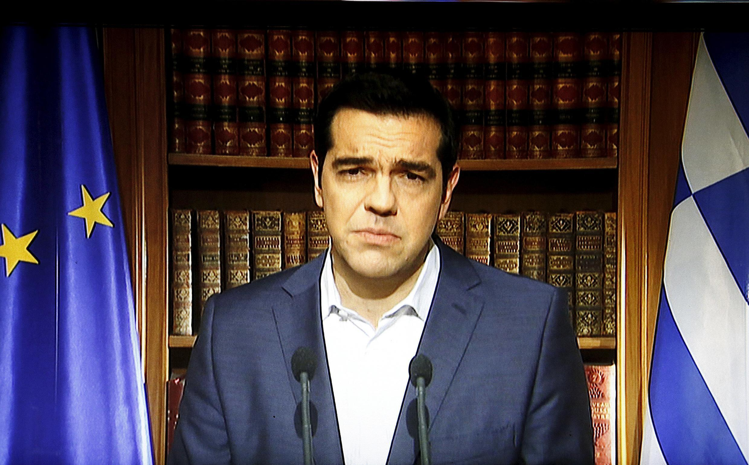 Greek Prime Minister Alexis Tsipras is seen on a television monitor while addressing the nation in Athens, Greece July 1, 2015.
