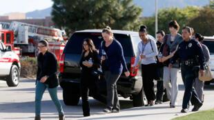 警察護送人群離開美國加州貝納迪諾市受到槍擊的樓房