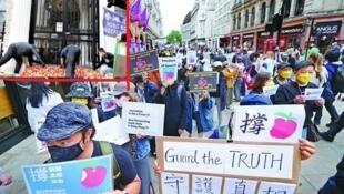 倫敦撐蘋果集會,示威者在中國駐英大使館前倒蘋果(小圖),以示對打壓新聞的不滿。