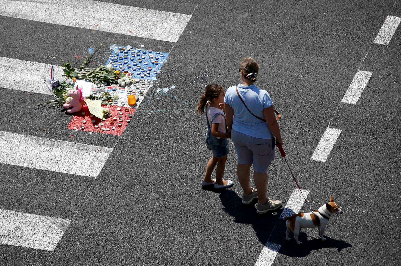 Uma mulher e sua filha andam perto de um memorial improvisado em Nice