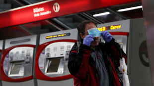 A metro passenger puts on a protective face mask that was given to him, as he goes to work during the coronavirus disease (COVID-19) lockdown in Madrid, Spain.