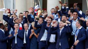El presidente francés Emmanuel Macron y su esposa Brigitte Macron posan con el capitán del equipo de fútbol de Francia Hugo Lloris sosteniendo el trofeo, en el Palacio del Elíseo en París, Francia, 16 de julio de 2018.