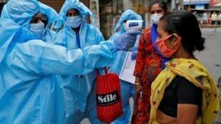 Un agent de santé utilise un thermomètre infrarouge pour vérifier la température d'une femme pour savoir si elle a développé des symptômes du coronavirus, dans un quartier résidentiel de Kolkata, en Inde, le 21 avril.